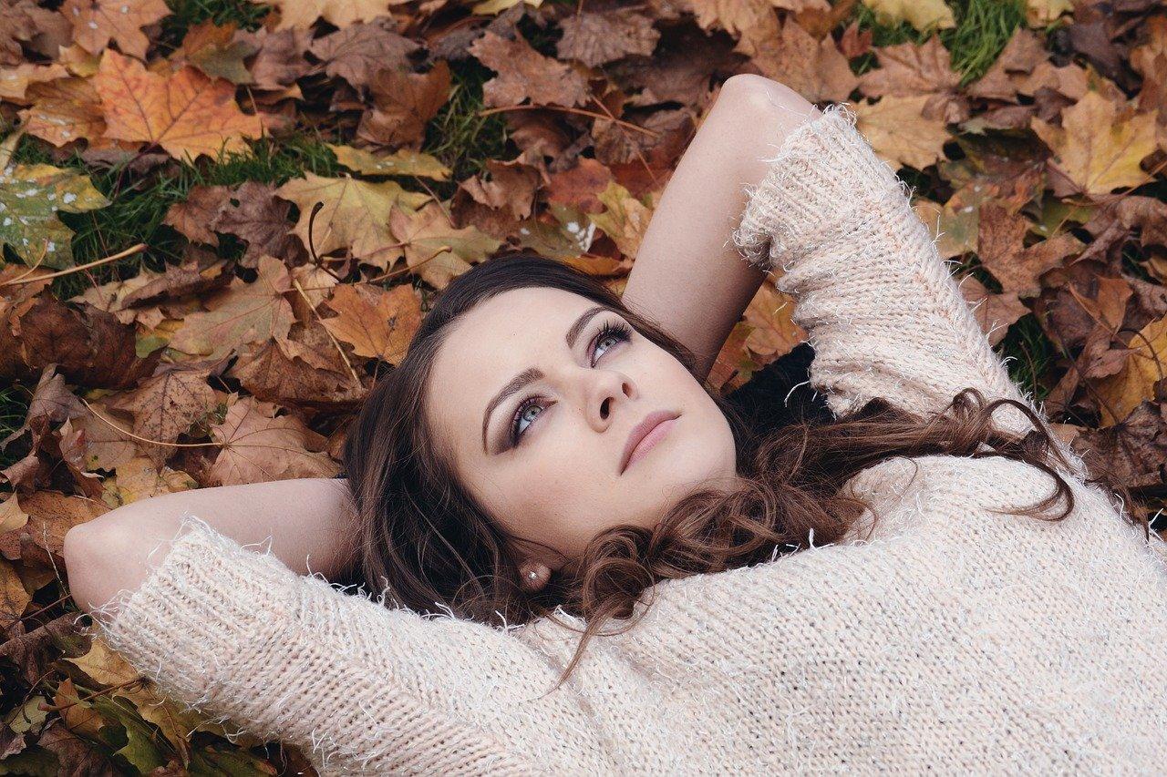 Frau liebt in Blätterhaufen Herbst nachhaltige Kleidung